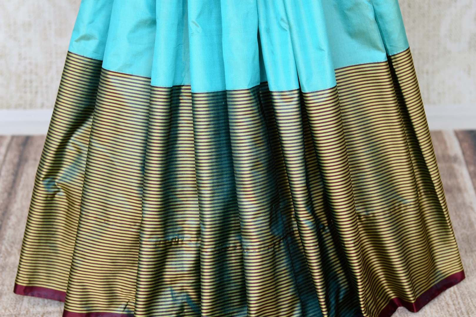 Shop turquoise blue Banarasi silk saree online in USA with striped border. Keep your wardrobe update with latest Indian handwoven sarees from Pure Elegance Indian fashion store in USA. Shop traditional Benarasi sarees, pure silk sarees for Indian women in USA from our online store.-pleats