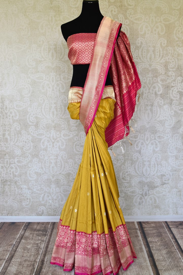 Shop mustard tussar Banarasi saree online in USA with pink zari border and pallu. Radiate traditional charm with beautiful Banarasi saris from Pure Elegance Indian clothing store in USA. Choose from a variety of Banarasi silk sarees, Banarasi georgette saris, Banarasi tussar sarees for special occasions.-full view
