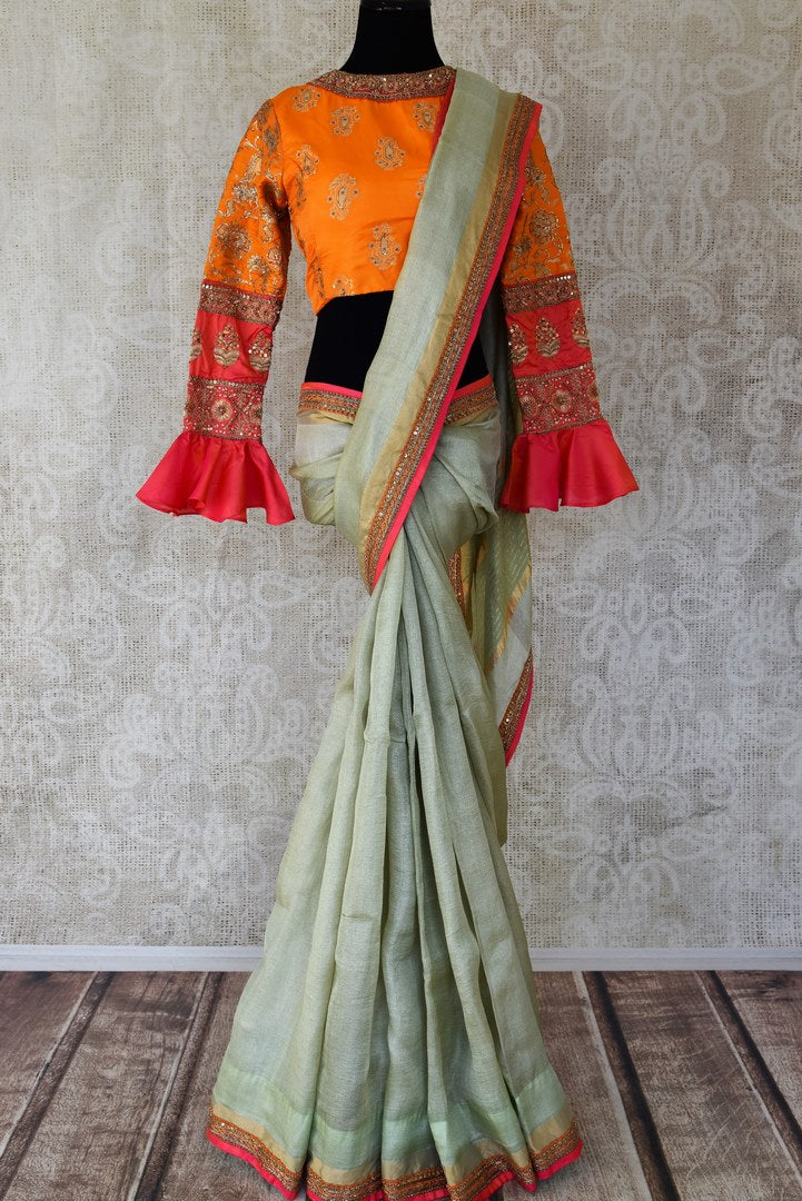 Shop powder green embroidered linen sari online in USA with orange embroidered saree blouse. Make fashionable choices with latest Indian designer saris from Pure Elegance Indian fashion store in USA. Shop traditional Kanchipuram silk sarees, Banarasi sarees, bridal sarees for Indian brides in USA from our online store.-full view