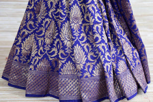 Buy white and blue muga Banarasi saree online in USA with floral zari work. Radiate traditional charm with beautiful Banarasi sarees from Pure Elegance Indian clothing store in USA. Choose from a variety of handwoven saris, Banarasi silk sarees, Banarasi georgette sarees, Banarasi tussar saris for special occasions.-pleats