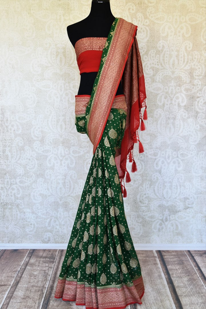 Shop green georgette Banarasi sari online in USA with red zari border. Feel traditional on special occasions in beautiful Indian designer saris from Pure Elegance Indian fashion store in USA. Choose from a splendid variety of Banarasi sarees, pure handwoven saris. Buy online.-full view