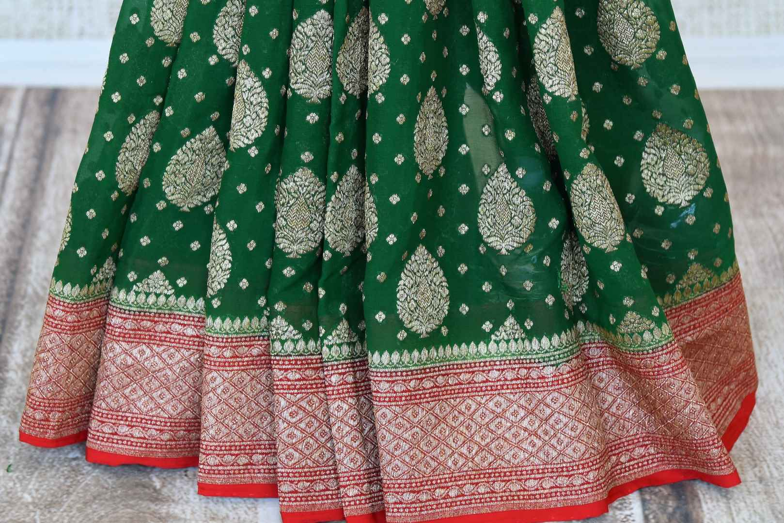 Shop green georgette Banarasi sari online in USA with red zari border. Feel traditional on special occasions in beautiful Indian designer saris from Pure Elegance Indian fashion store in USA. Choose from a splendid variety of Banarasi sarees, pure handwoven saris. Buy online.-pleats
