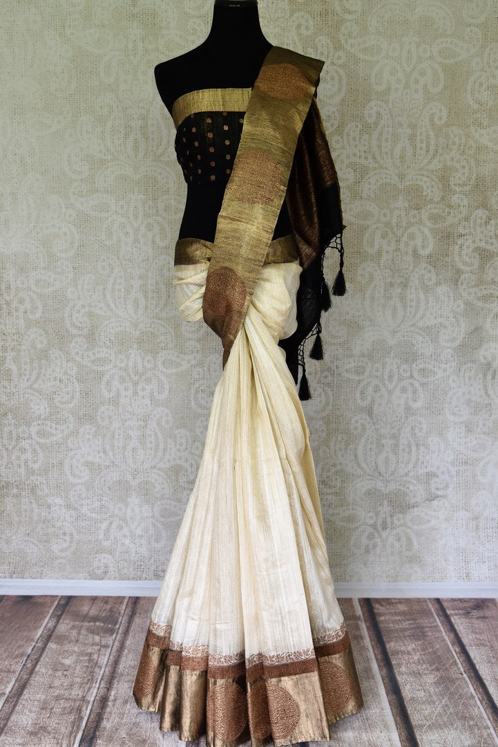 Shop off-white tussar Benarasi saree online in USA with black golden zari border. Be an epitome of elegance in exquisite Banarasi saris from Pure Elegance Indian clothing store in USA.-full view
