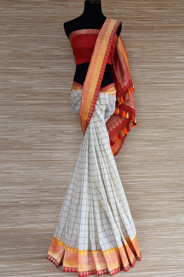 Buy white check linen saree online in USA with red and orange zari border. Select your favorite Indian sarees, pure silk sarees, wedding sarees from Pure Elegance Indian fashion store in USA for weddings and special occasions.- full view