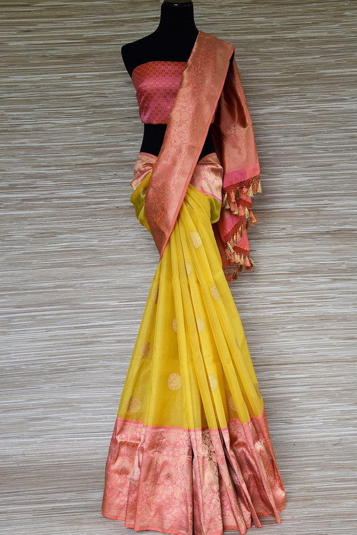 Buy stunning yellow tissue silk Banarasi saree online in USA with pink zari border. Be a stunner on special occasions in exquisite Banarasi silk sarees, handwoven saris from Pure Elegance Indian fashion store in USA for Indian women.-full view