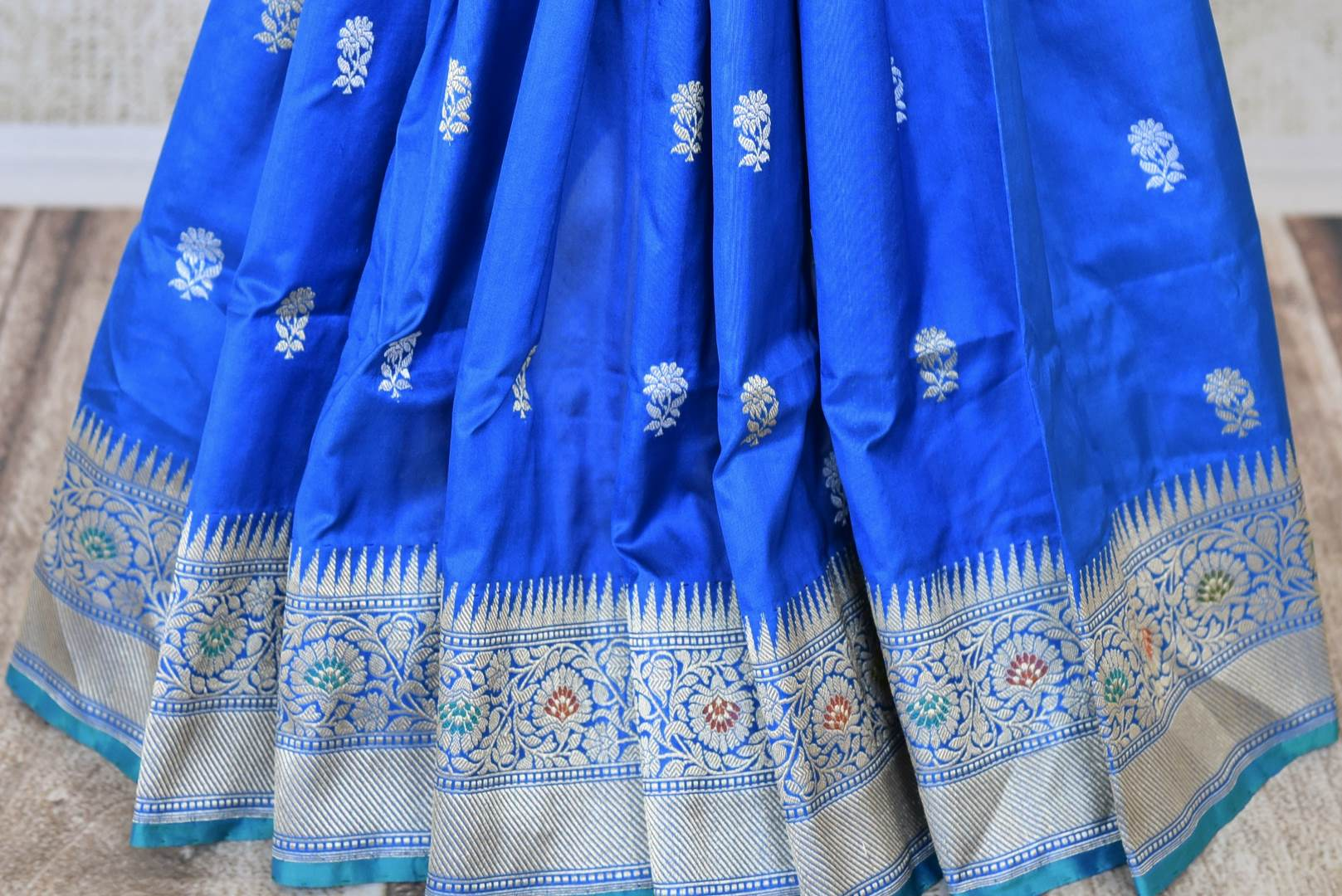 Buy blue Banarasi silk sari online in USA with flower buta and zari minakari border. Raise your ethnic style quotient at weddings and special occasions with exquisite Indian sarees from Pure Elegance Indian clothing store in USA. Pick from a tasteful collection of handloom sarees, pure silk sarees, Banarasi saris. Shop now.-pleats