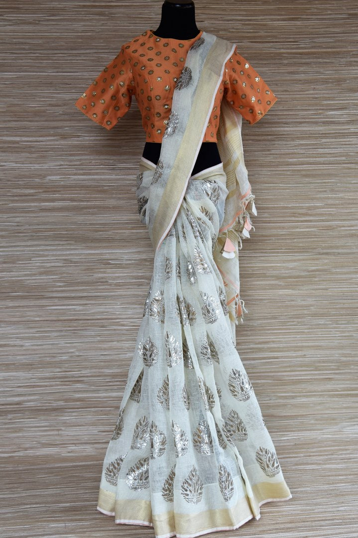 Buy cream linen sari online in USA with floral print and orange sari blouse. Select your favorite Indian sarees, pure silk sarees, wedding sarees from Pure Elegance Indian fashion store in USA for weddings and special occasions.-full view
