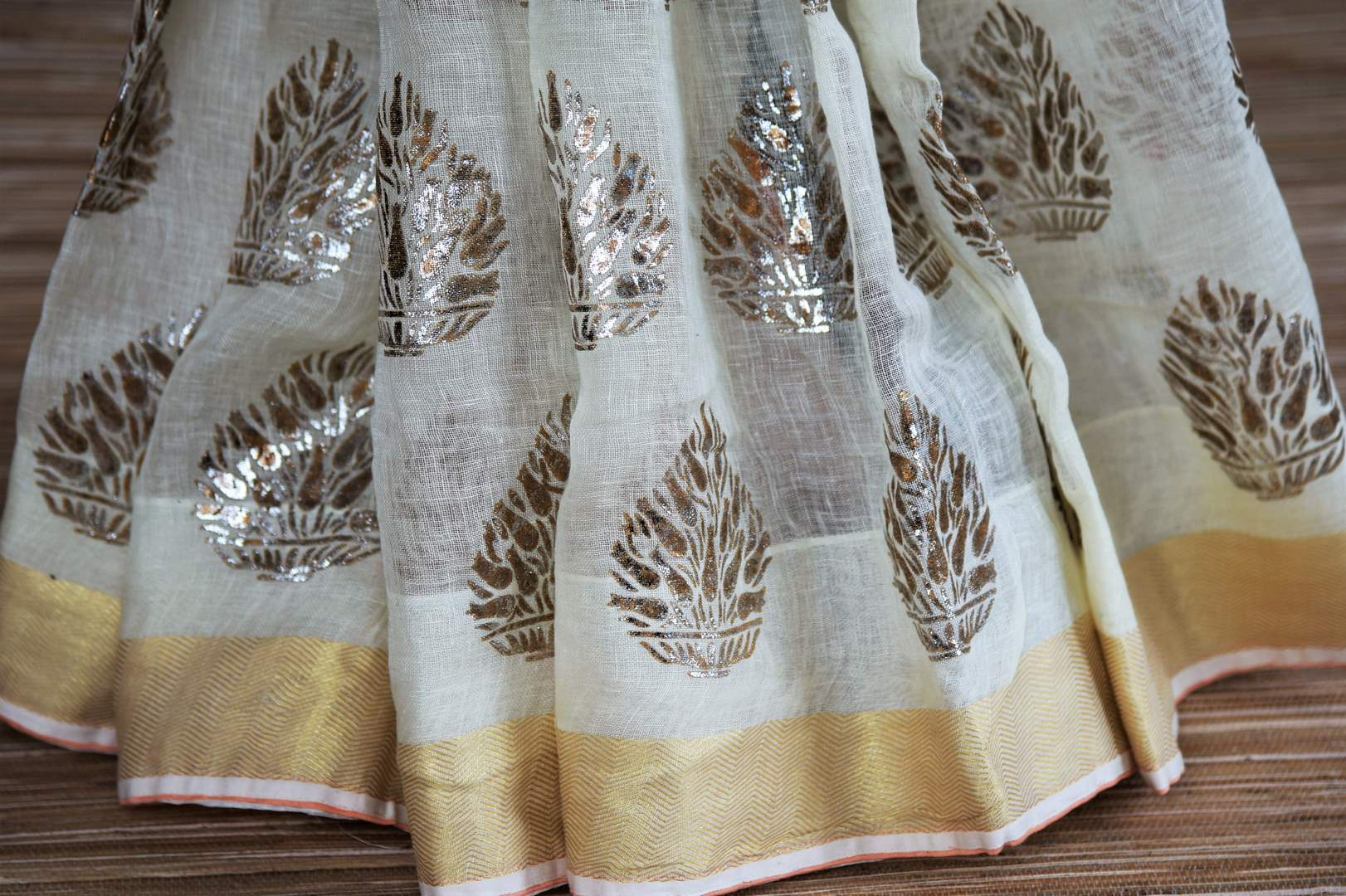 Buy cream linen sari online in USA with floral print and orange sari blouse. Select your favorite Indian sarees, pure silk sarees, wedding sarees from Pure Elegance Indian fashion store in USA for weddings and special occasions.-pleats