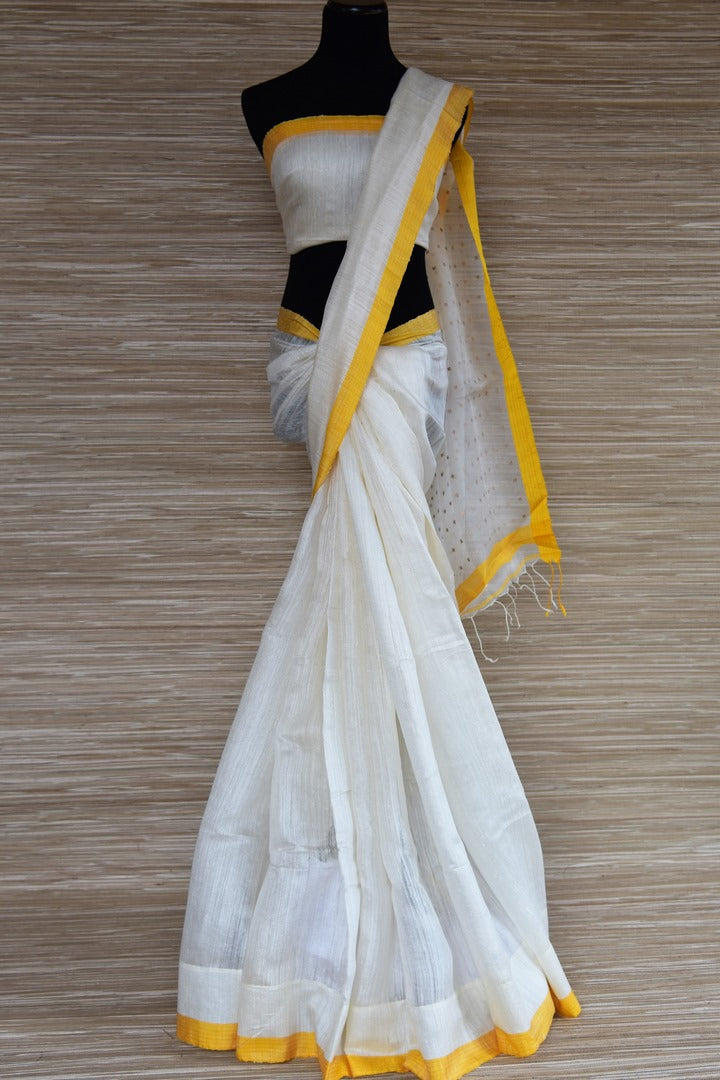 Shop white matka silk saree online in USA with yellow border. Select your favorite Indian handloom sarees, pure silk sarees, wedding sarees from Pure Elegance Indian fashion store in USA for weddings and special occasions.-full view