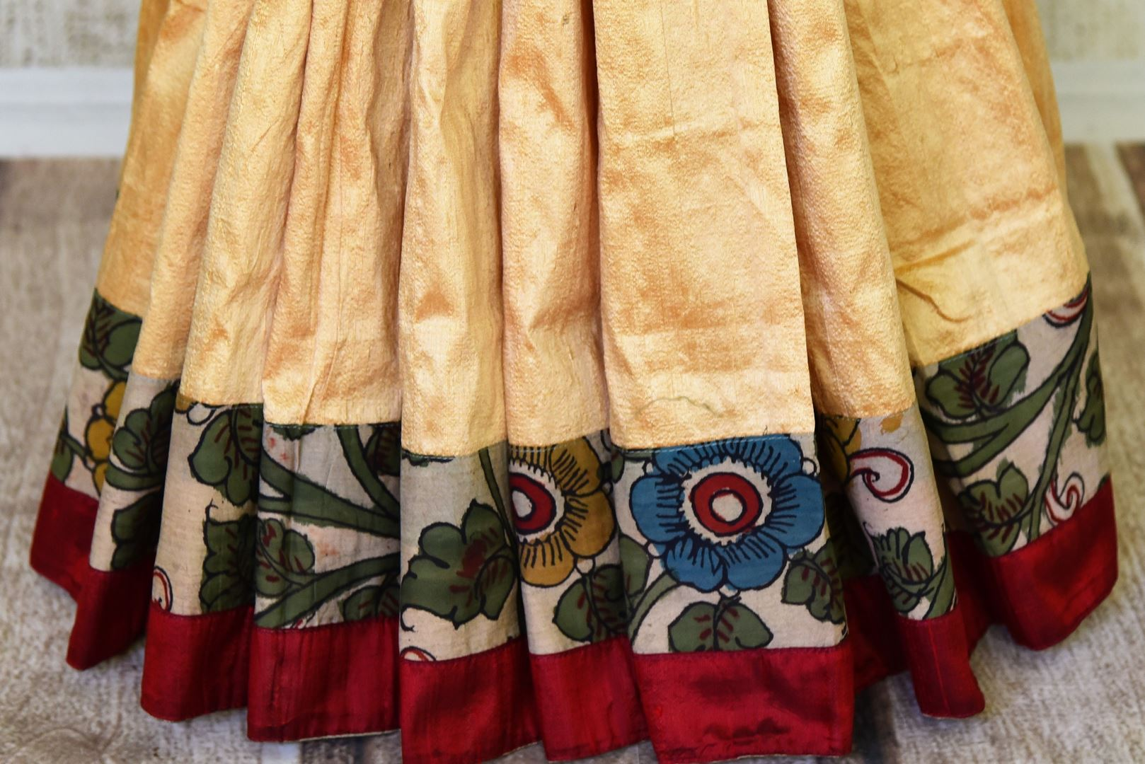 Buy graceful cream raw silk sari online in USA with hand painted Kalamkari border and black sari blouse. Elevate your traditional glam on weddings and special occasions with an exclusive range of handwoven sarees, designer saris especially for Indian women in USA at Pure Elegance Indian fashion store. Shop now.-pleats