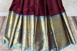 Shop plum color Kanjivaram sari online in USA with blue zari border. Enhance your ethnic style with exquisite Kanchipuram silk sarees from Pure Elegance Indian clothing store in USA.-pleats