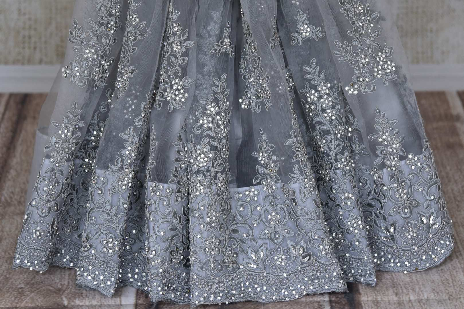 Shop beautiful grey pearl and stone net sari online in USA. Bring up your style game with stunning designer sarees, wedding sarees, Bollywood sarees from Pure Elegance Indian boutique in USA.-pleats