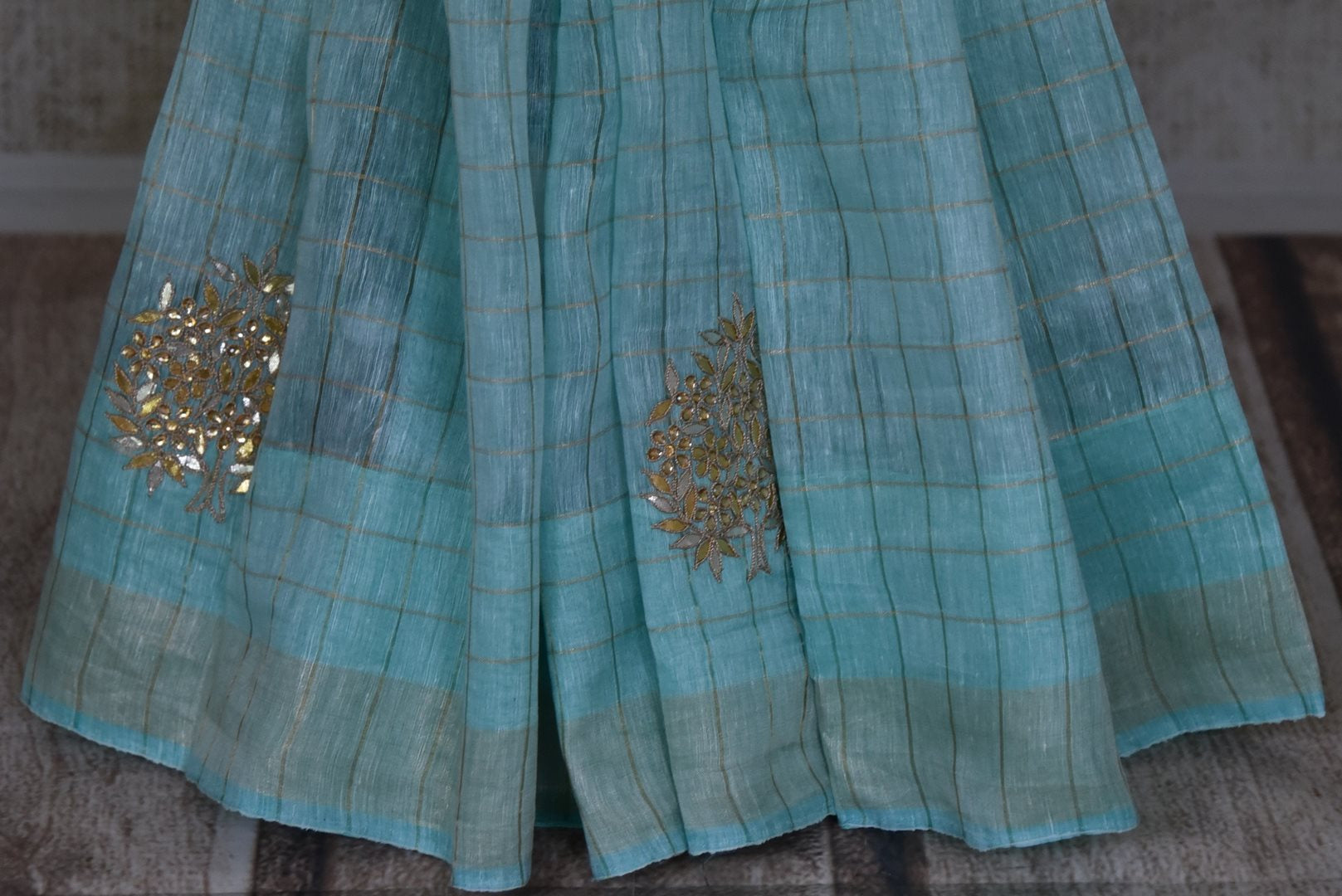 Shop beautiful light blue gota patti work check linen sari online in USA. Be the talk of parties and weddings with exquisite handloom sarees, embroidered sarees from Pure Elegance Indian clothing store in USA. Shop online now.-pleats