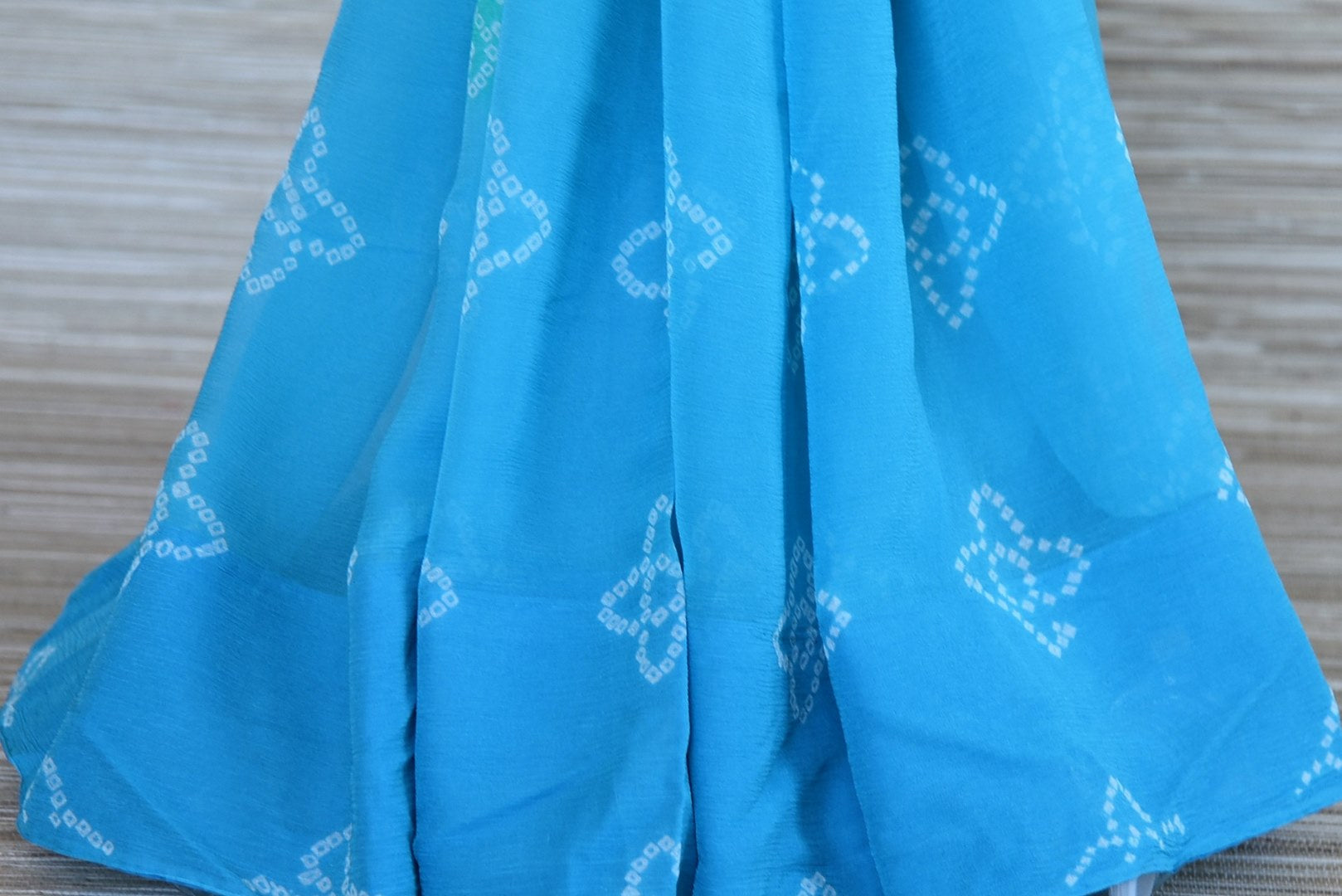 Shop elegant sky blue Bandhej chiffon saree online in USA with embroidered green saree blouse. Be an epitome of elegance and tradition in exquisite designer saris, handwoven saris from Pure Elegance clothing store in USA. -pleats