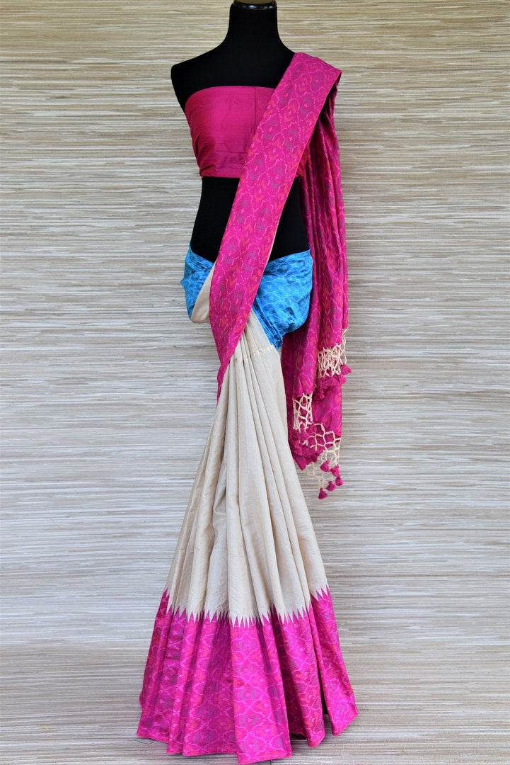 Shop gorgeous cream tussar raw silk sari online in USA with blue and pink ikat border. Grab exquisite handwoven sarees, embroidered saris, pure silk sarees for the coming festive and wedding season from Pure Elegance Indian boutique in USA. Shop online now.-full view
