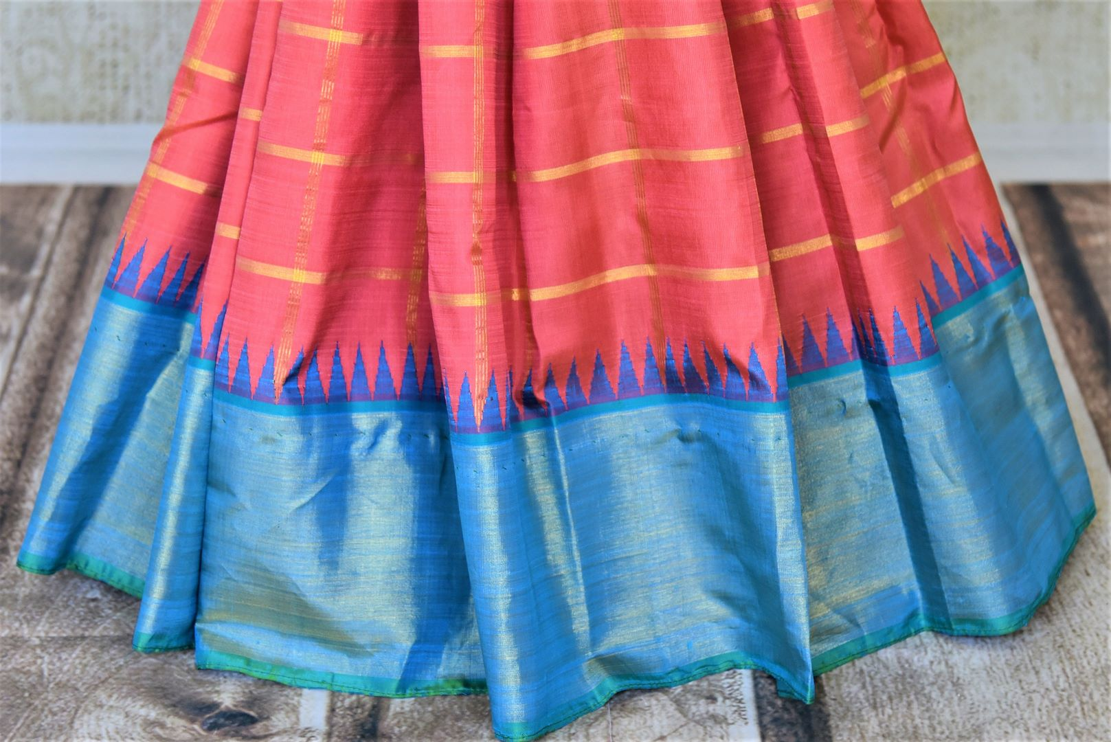 Shop coral zari check Kanchipuram sari online in USA with blue zari border and zari pallu. Go for rich traditional festive look with beautiful Kanchipuram silk sarees, soft silk sarees, Banarasi silk saris from Pure Elegance Indian cloth store in USA. -pleats