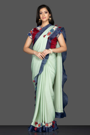 Shop beautiful mint green embroidered sari online in USA with blue ruffle border and maroon saree blouse. Elevate your sartorial choice with exclusive Indian designer sarees with blouse, embroidered sarees, pure silk sarees from Pure Elegance Indian fashion store in USA.-front