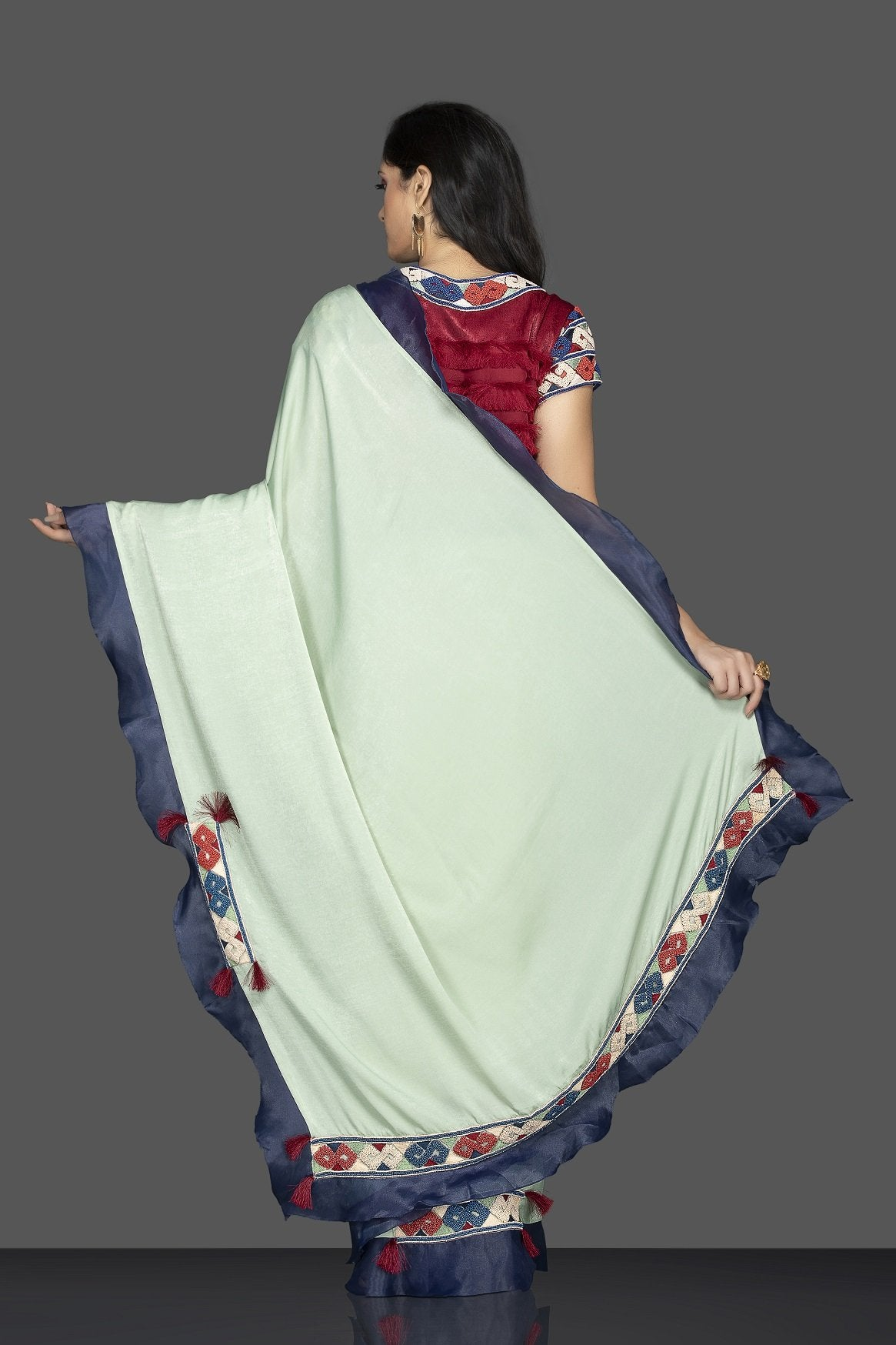 Shop beautiful mint green embroidered sari online in USA with blue ruffle border and maroon saree blouse. Elevate your sartorial choice with exclusive Indian designer sarees with blouse, embroidered sarees, pure silk sarees from Pure Elegance Indian fashion store in USA.-back