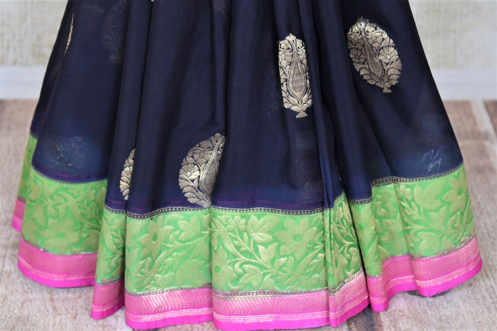 Shop gorgeous black organza Banarasi sari online in USA with green foliate zari border and zari buta. Make your saree wardrobe rich and colorful with stunning handwoven sarees, pure silk sarees, designer sarees from Pure Elegance Indian clothing store in USA.-pleats