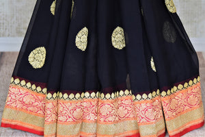 Buy captivating black floral zari buta georgette Banarasi saree online in USA. Go for an extraordinary traditional look with splendid handwoven sarees, embroidered sarees with blouses, Banarasi saris from Pure Elegance from Indian cloth store in USA.  Shop online or visit our store now.-pleats