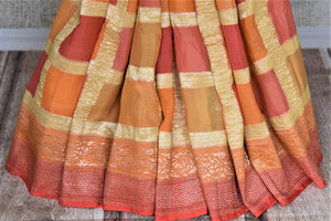 Buy lovely orange and pink zari check georgette Banarasi sari online in USA. Go for an extraordinary traditional look with splendid handwoven sarees, embroidered sarees with blouses, Banarasi saris from Pure Elegance from Indian cloth store in USA.  Shop online or visit our store now.-pleats
