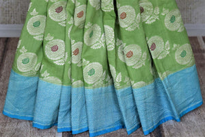 Shop light green muga Benarasi saree online in USA with blue zari border and marigold buta. Make your saree wardrobe rich and colorful with stunning handwoven sarees, pure silk sarees, designer sarees from Pure Elegance Indian clothing store in USA.-pleats