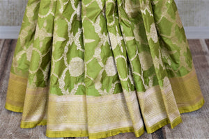 Buy pistachio green Benarasi silk saree online in USA with yellow zari border. Make your saree wardrobe rich and colorful with stunning handwoven sarees, pure silk sarees, designer sarees from Pure Elegance Indian clothing store in USA.-pleats