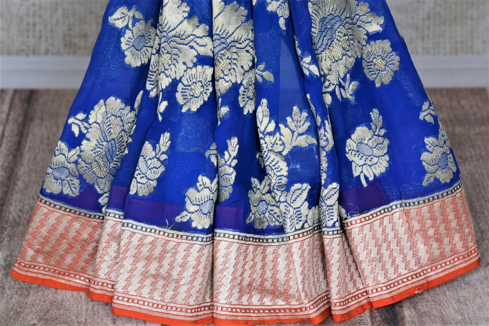 Buy beautiful indigo blue silver floral zari work georgette Banarasi saree online in USA. Go for an extraordinary traditional look with splendid handwoven sarees, embroidered sarees with blouses, Banarasi saris from Pure Elegance from Indian cloth store in USA.  Shop online or visit our store now.-pleats