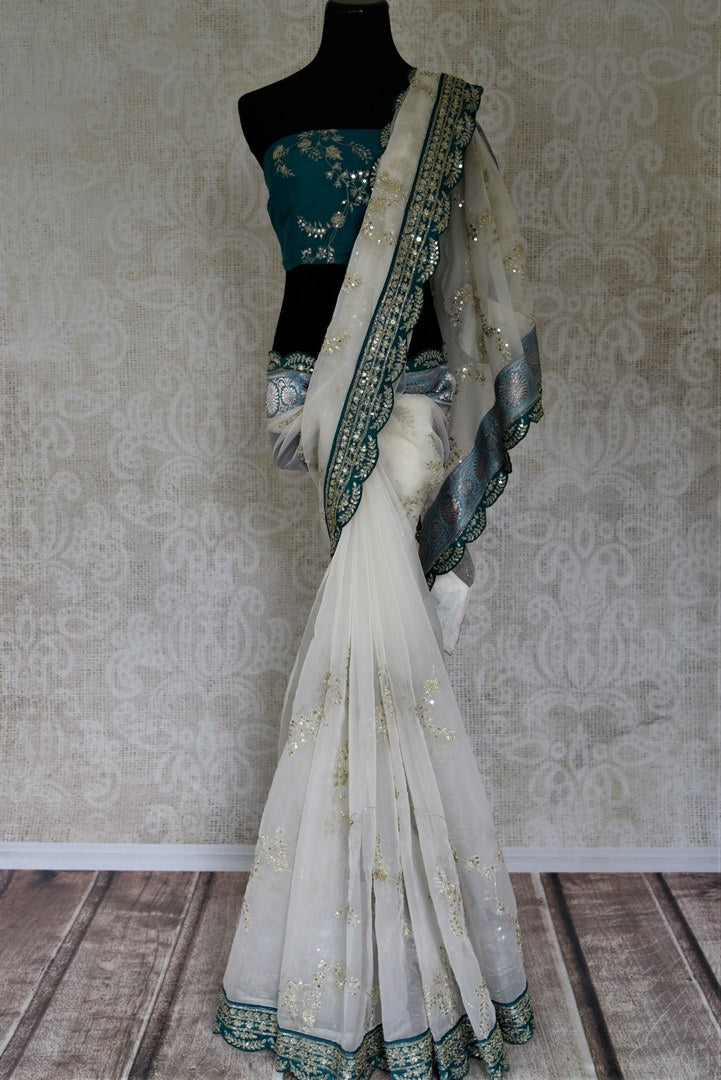 Stunning off-white embroidered organza saree for online shopping in USA with green embroidered border. Buy exquisite handwoven sarees with blouse from Pure Elegance Indian clothing store in USA for parties and festive occasions.-full view