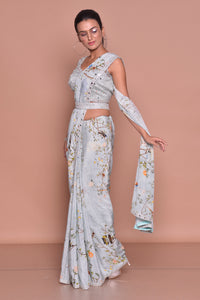 Shop powder blue floral belted saree online in USA with embroidered sleeveless saree blouse. Look fashionable on special occasions in contemporary sarees, designer sarees with blouse, embroidered saris from Pure Elegance Indian luxury clothing store in USA.-full view