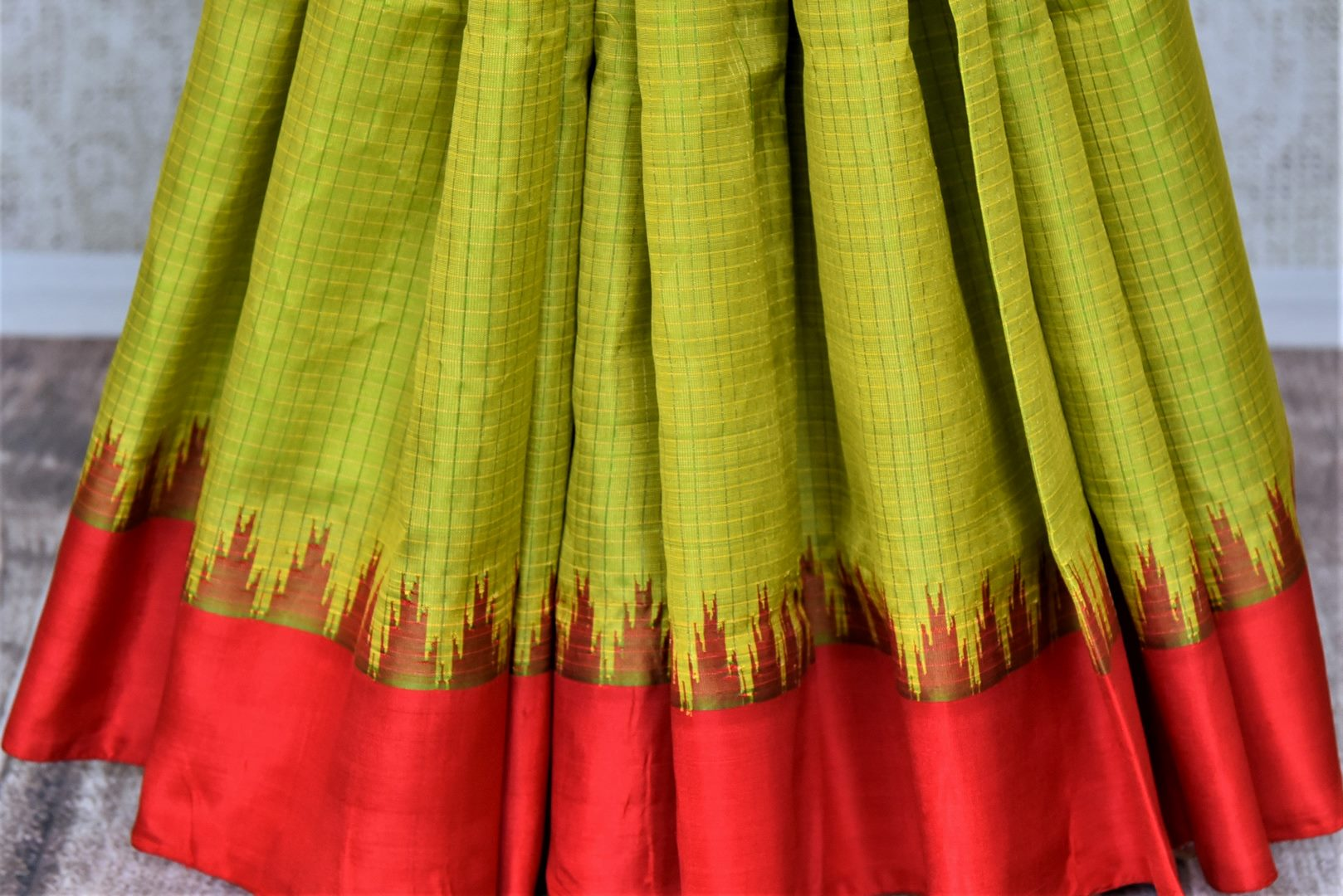 Shop gorgeous pistachio green check Gadhwal silk saree online in USA with solid red border. Let your elegance be the highlight of every occasion with stunning handwoven saris, soft silk sarees, traditional Kanchipuram sarees from Pure Elegance Indian fashion boutique in USA.-pleats