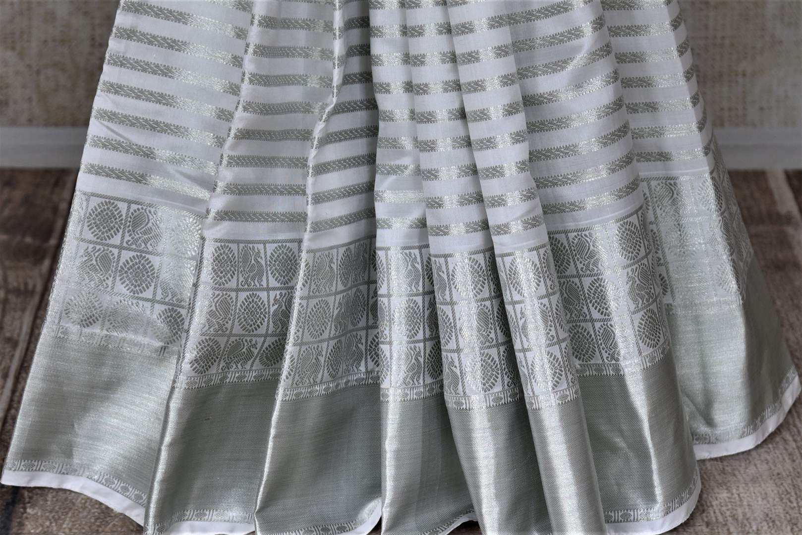 Shop elegant white zari stripes Kanjivaram sari online in USA. Let your elegance be the highlight of every occasion with stunning handwoven sarees, soft silk sarees, traditional Kanchipuram sarees from Pure Elegance Indian fashion boutique in USA.-pleats