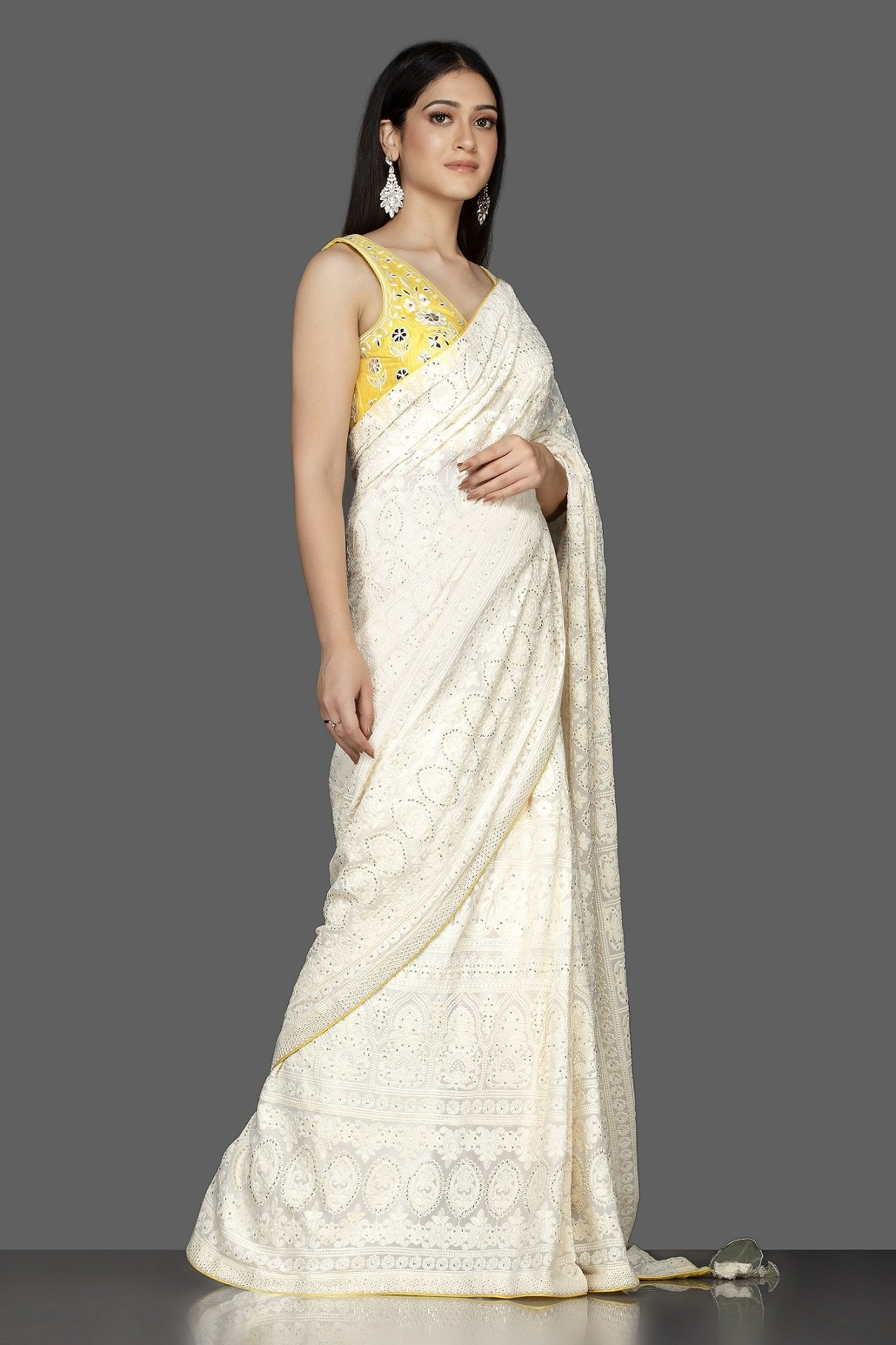 Shop beautiful off-white Lucknowi georgette saree online in USA with yellow embroidered saree blouse. Spread ethnic elegance on weddings and special occasions in splendid designer sarees with blouses, embroidered saris crafted with exquisite Indian craftsmanship from Pure Elegance Indian fashion store in USA.-side