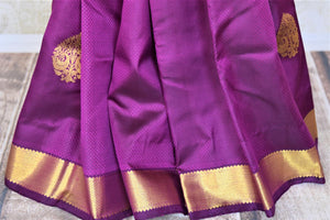 Buy attractive purple Kanjivaram sari online in USA with golden zari border and zari buta. Add spark to your festive style with beautiful Kanchipuram silk sarees in USA from Pure Elegance Indian fashion store.-pleats