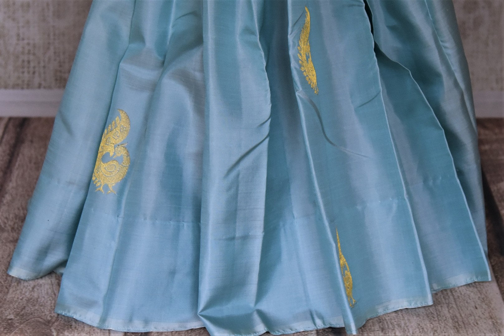 Buy gorgeous powder blue borderless Kanjivaram saree online in USA with zari peacock buta and purple zari pallu. Add spark to your festive style with beautiful Kanchipuram silk saris in USA from Pure Elegance Indian fashion store.-pleats