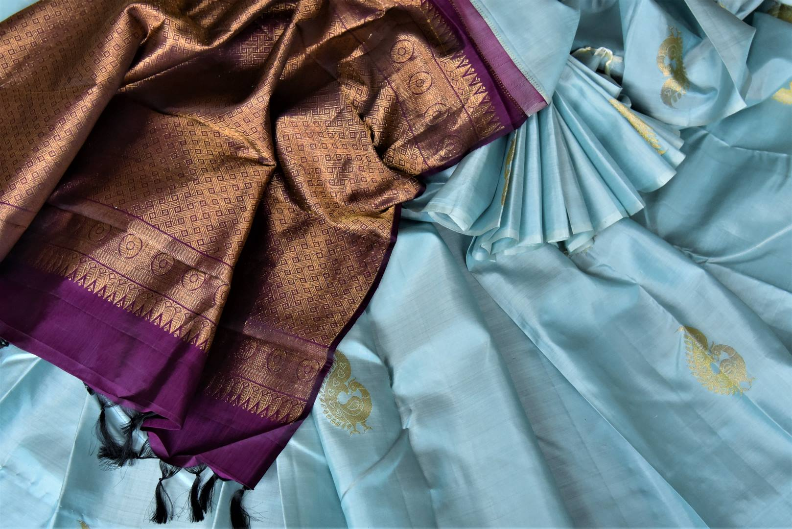 Buy gorgeous powder blue borderless Kanjivaram saree online in USA with zari peacock buta and purple zari pallu. Add spark to your festive style with beautiful Kanchipuram silk saris in USA from Pure Elegance Indian fashion store.-details