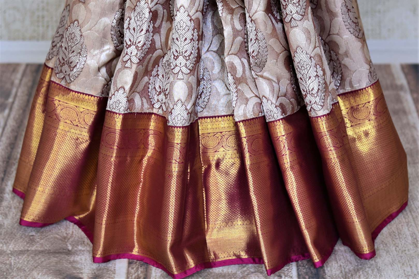 Buy beige Kanjeevaram sari online in USA with silver zari buta and magenta zari border. Get spoiled for choices with a myriad of Kanjivaram silk sarees, wedding sarees from Pure Elegance Indian fashion store in USA.-pleats