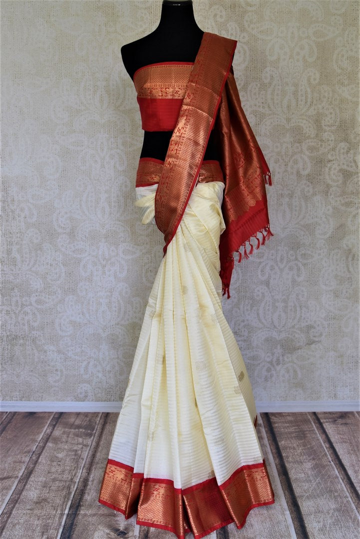 Shop cream self stripes Kanjivaram sari online in USA with red zari border. Get spoiled for choices with a myriad of Kanjivaram silk sarees, wedding sarees from Pure Elegance Indian fashion store in USA.-full view