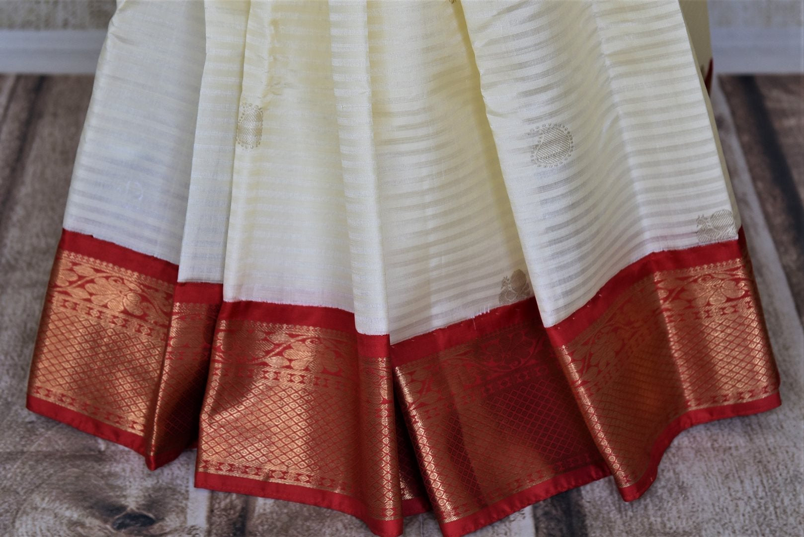 Shop cream self stripes Kanjivaram sari online in USA with red zari border. Get spoiled for choices with a myriad of Kanjivaram silk sarees, wedding sarees from Pure Elegance Indian fashion store in USA.-pleats