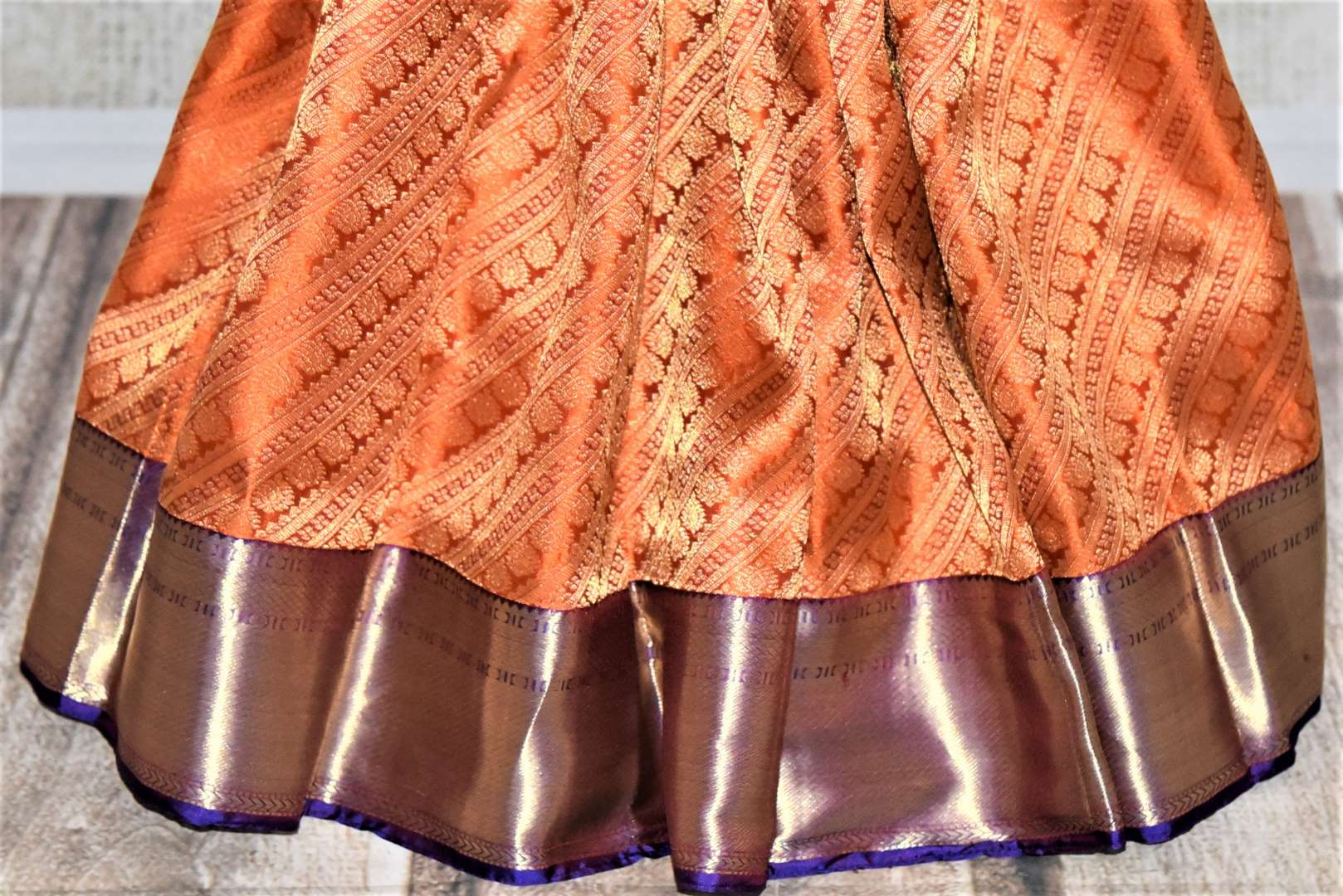Buy orange heavy Kanjivaram saree online in USA with blue zari border. Look beautiful on weddings with exquisite Kanjivaram sarees from Pure Elegance Indian fashion store in USA. Get spoiled for choices with a myriad of pure silk sarees, Kanjeevaram saris available online.-pleats