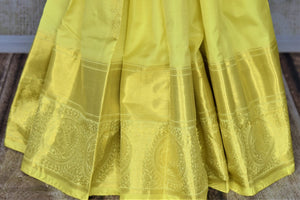Buy lovely lemon yellow Kanjivaram saree online in USA with golden zari buta and zari border. Look rich and traditional at weddings and festive occasions with exquisite Kanchipuram silk sarees from Pure Elegance Indian fashion store in USA.-pleats
