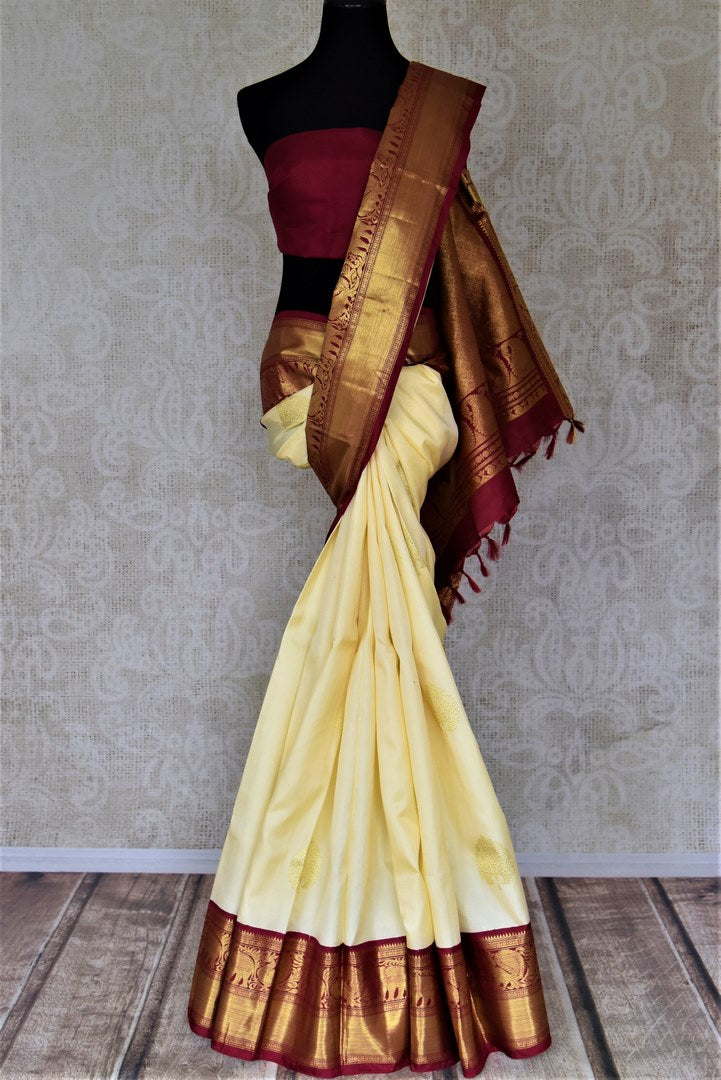 Shop elegant cream Kanjeevaram saree online in USA with maroon golden zari border. Make a beautiful appearance on special occasions with exquisite Indian designer sarees, Kanchipuram silk saris, Bollywood sarees from Pure Elegance Indian fashion store in USA.-full view