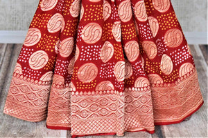 Shop ethnic red georgette Banarasi sari online in USA with bandhej print. Spread your ethnic charm on special occasions with traditional Banarasi sarees, bandhej sarees, georgette sarees from Pure Elegance Indian fashion store in USA.-pleats