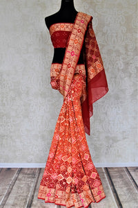 Shop beautiful orange and red georgette Banarasi bandhej sari online in USA. Spread your ethnic charm on special occasions with traditional Banarasi sarees, bandhej sarees, georgette sarees from Pure Elegance Indian fashion store in USA.-full view