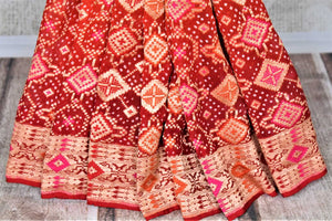 Shop beautiful orange and red georgette Banarasi bandhej sari online in USA. Spread your ethnic charm on special occasions with traditional Banarasi sarees, bandhej sarees, georgette sarees from Pure Elegance Indian fashion store in USA.-pleats
