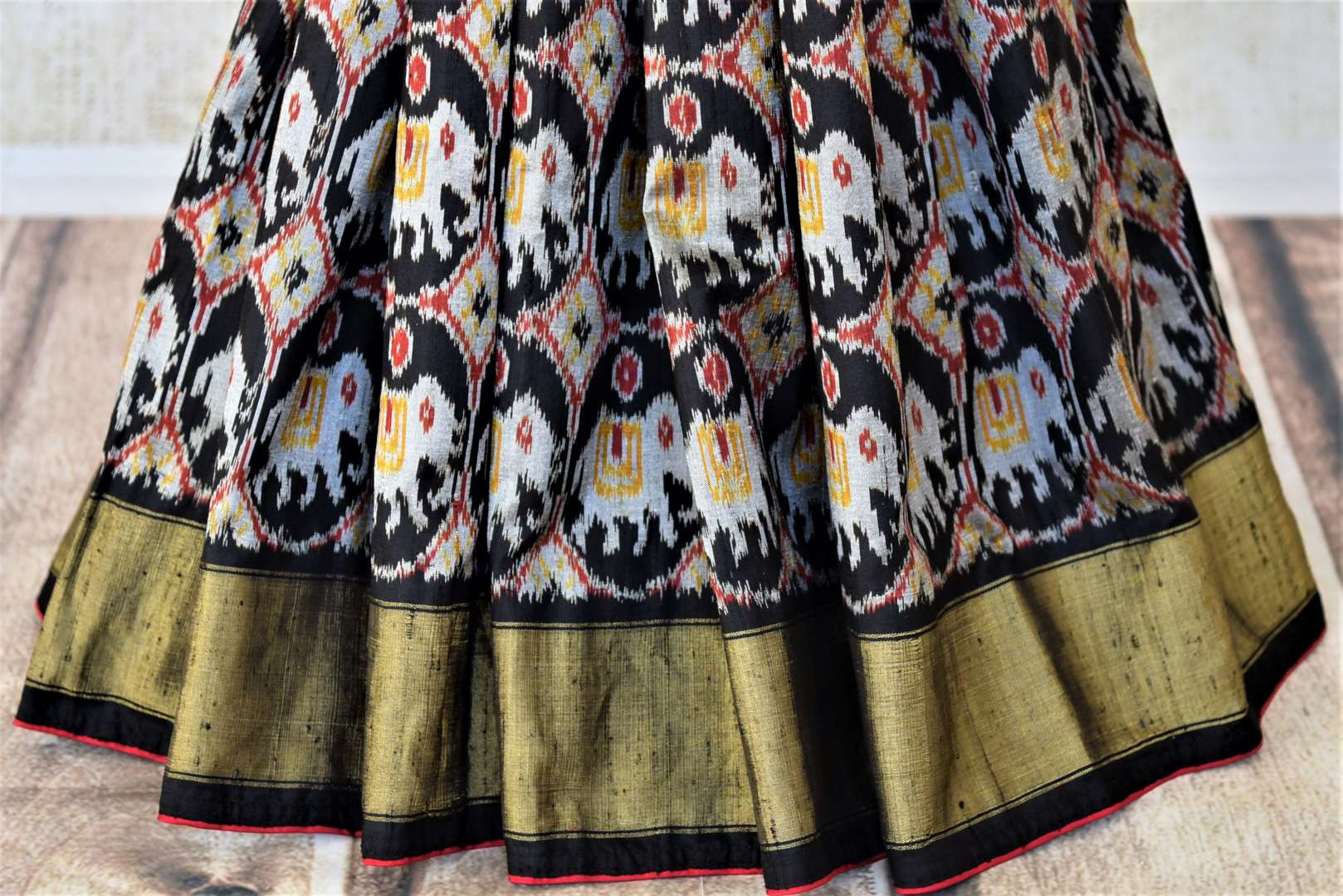 Shop gorgeous red and black patola silk saree online in USA with embroidered blouse. Keep it light yet festive on special occasions with beautiful silk saris, patola sarees from Pure Elegance Indian fashion store in USA.-pleats