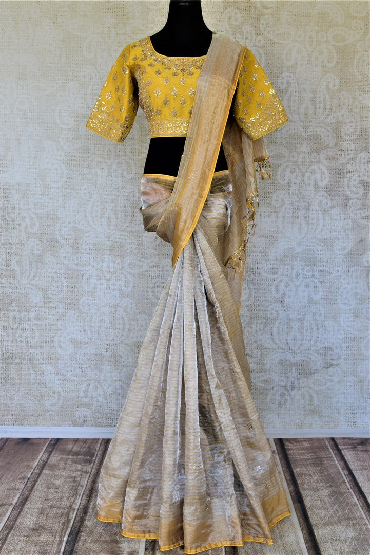 Buy beautiful beige gota patti zari tissue saree online in USA with yellow embroidered blouse. Be the center of attraction at parties and weddings with beautiful tussar silk sarees, pure silk sarees, embroidered sarees, handloom saris from Pure Elegance Indian fashion store in USA.-full view