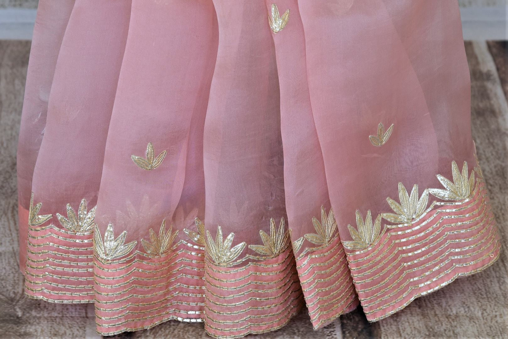 Shop stunning baby pink organza saree online in USA with gota work border. Keep it light yet festive on special occasions with beautiful organza silk saris from Pure Elegance Indian fashion store in USA.-pleats