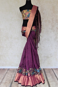 Buy purple linen sari online in USA with Kalamkari applique and golden zari border. Be the talk of the occasions in exquisite linen sarees, embroidered saris from Pure Elegance Indian fashion store in USA. -full view