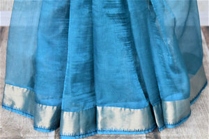 Shop light blue metallic linen saree online in USA with silver zari border. Be the talk of the occasions in exquisite linen sarees, embroidered saris from Pure Elegance Indian fashion store in USA. -pleats